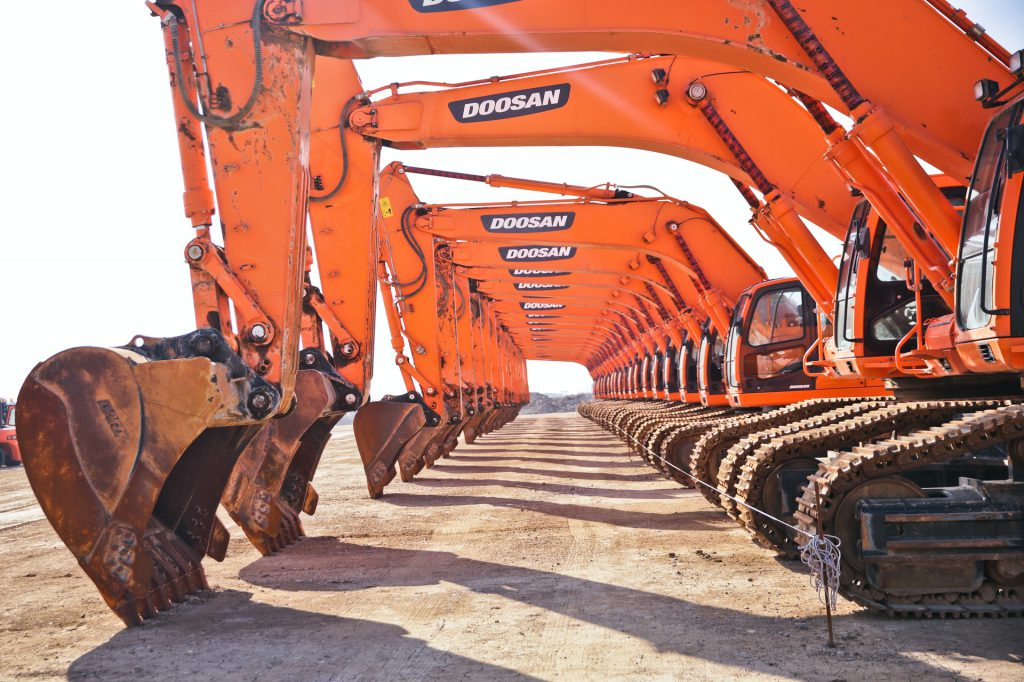 Several orange backhoes lined up in a row