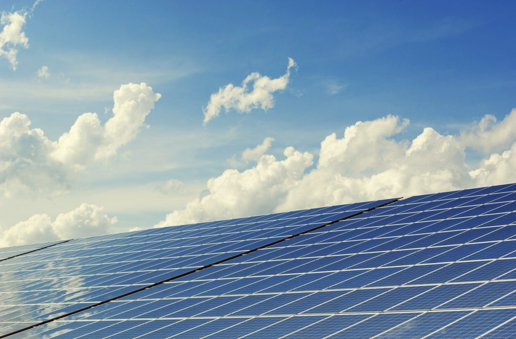 large blue solar panels with white clouds reflection