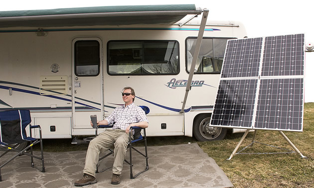 Man sitting outside of RV beside a panel of solar batteries