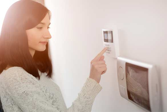 Woman activating a home alarm system